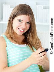 cellphone, lei, soggiorno, sorridente, texting, donna, giovane
