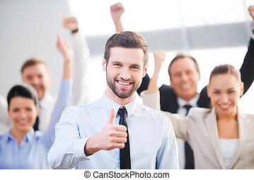 fiducioso, sentimento, uomo affari, su, felice, fondo, pollice, team., esposizione, posizione sorridente, suo, colleghi, mentre