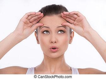 fronte, donna, wrinkles., lei, su, isolato, giovane guardare, mentre, toccante, bianco, sorpreso