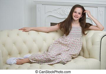 sedendo ragazza, giovane, divano, bello, caminetto