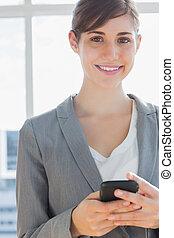 sorridente, macchina fotografica, texting, donna d'affari