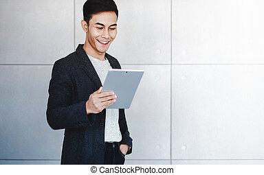 standing, felice, usando, dati, lettura, industriale, digitale, giovane, uomo affari, tablet., concreto, sorridente, ritratto, wall.