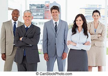 standing, suo, colleghi, sorridente, mezzo, esecutivo, giovane, stanza
