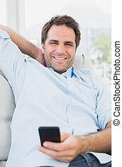 telefono, vivente, casa, suo, seduta, dall'aspetto, divano, sorridente, macchina fotografica, texting, uomo, stanza