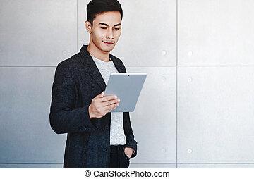 wall., lettura, uomo affari, giovane, usando, sorridente, concreto, ritratto, felice, industriale, digitale, dati, standing, tablet.
